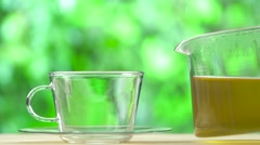 Steaming Cup of tea and teapot on blur green background Stock Footage