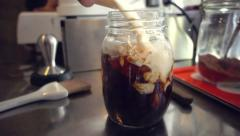 Barista mixing fresh milk into 2 shots of fresh coffee on ice, slow motion - stock footage