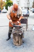 Blacksmith handles the horseshoe on the anvil at the outdoors Kuvituskuvat