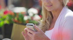 4K Portrait of beautiful mature woman looking at mobile phone outdoors in city - stock footage