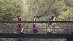 Beautiful Young Women Cross A Bridge In A Beautiful Lush Forest (4K) Stock Footage