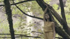 Beautiful Mixed Race Model Poses In A Tree, Waterfall In Background (4K) Stock Footage