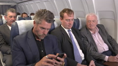 Male business team on plane get positive good news phone call Stock Footage