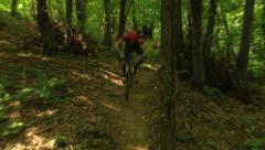 Action shot of a pro downhill cyclist riding and jumping on a little hill Stock Footage