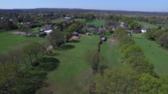 4K Aerial flight above forest fields & farm buildings in the English countryside Stock Footage