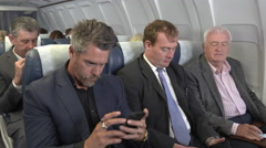 Bad news mobile phone call for male business team on plane Stock Footage