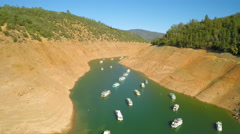 An aerial view over a very low Oroville Lake in California during extreme Stock Footage