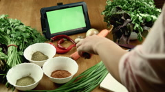 The woman cleans carrot and watches the recipe in the tablet Stock Footage