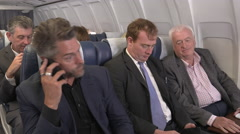 Male business travellers get bad news cell phone call when they are on a plane Stock Footage