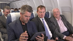 Male business team on plane get positive good news E-mail Stock Footage
