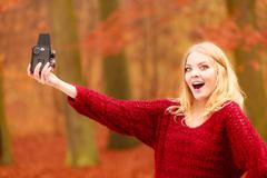 Woman with old vintage camera taking selfie photo. - stock photo