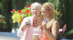 4K Attractive smiling mother & daughter pose to take a selfie with mobile phone. Stock Footage