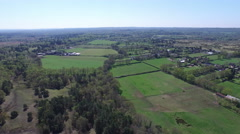 4K Aerial flight above forest & fields in the English countryside Stock Footage