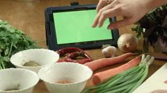 The woman cooks food and watches the recipe in the tablet - stock footage