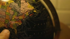 A man checking out geography on a globe Stock Footage