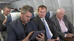 Bad news E-mail for male business team on plane Stock Footage