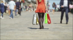 4K Back view of young woman walking away from camera in busy shopping area Stock Footage