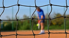 Tennis Player serving Tennis Ball With Tennis Racket On Clay Court, net in front Stock Footage