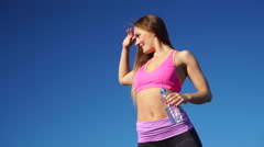 Stock Video Footage of Woman drinking water after sport gym against blue sky 4K