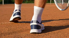 The legs of a Tennis Player serving Tennis Ball With Tennis Racket On Clay Court - stock footage