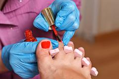 Chiropody Spa salon. Applying gel nail polish. - stock photo