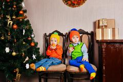 Brother and sister eating apples near a Christmas tree. Stock Photos