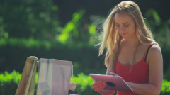 4K Portrait of beautiful young woman using computer tablet in the park Stock Footage