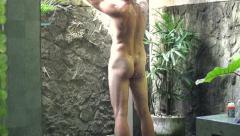 Young naked man washing body under shower, super slow motion, shot at 240fps - stock footage
