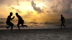 Silhouettes playing soccer on the beach with summer sunset vibrant colors. 4k Stock Footage