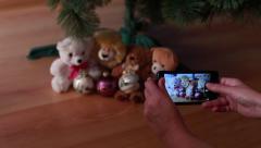 Girl photographs toys on the Christmas tree Stock Footage