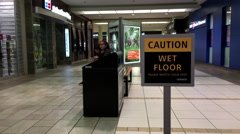 Close up wet floor caution sign inside shopping mall - stock footage