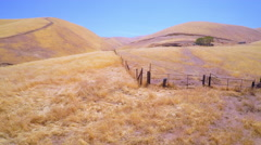 An aerial over the yellow brush covered rolling hills of Central California. - stock footage