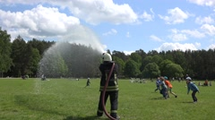 Firefighter with hose spray water under cheerful children. 4K Stock Footage
