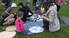 Kids with parents construct handmade kite on park meadow. 4K Stock Footage