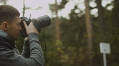 Male photographer is taking photographs in a forest at autumn time Stock Footage