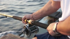 A fishing rod in strong hands. Sea fishing Stock Footage