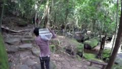 Young man carrying large big block of ice cube up a hill tropical rain forest 4k Stock Footage