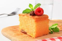 slice of homemade sponge cake on wooden cutting board - stock photo