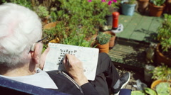 4K Elderly man in the garden doing a crossword puzzle in the newspaper Arkistovideo