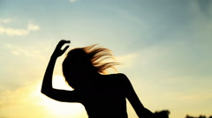 Silhouette of the woman dancing during beautiful sunset. Natural light and - stock footage