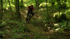 Action shot of a pro downhill cyclist driving fast past the camera Stock Footage