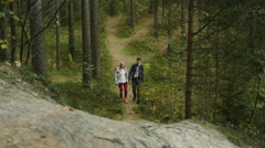 Couple is walking and going uphill in an autumn forest trail Stock Footage