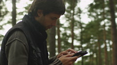 Long haired man in dark autumn clothes is standing in a forest and using tablet Stock Footage