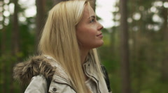 Blond woman in white autumn coat is standing in a forest and looking around Stock Footage
