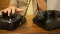 Office clerk man checks for dial tones onhis telephones Stock Footage