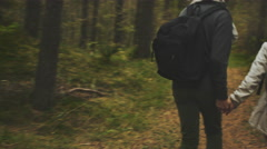 Couple with backpacks is running away from the camera while holding hands Stock Footage