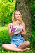 Blonde with a notebook and pen sitting near a tree Stock Photos