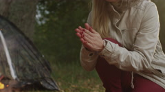 Portrait of a blond woman warming her hands near a campfire in a forest - stock footage