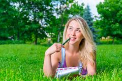 Happy Girl European appearance on the grass with notebook and pen - stock photo