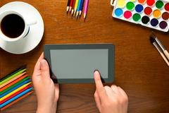tablet and drawing tools on the table and hands - stock photo